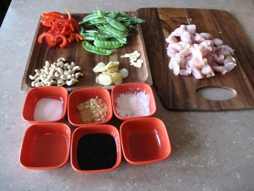 ingredients needed for Cashew Chicken Stir Fry in wooden board and red cups
