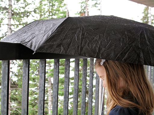 close up of a girl and black umbrella during the rain