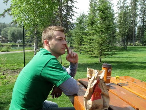 man wearing green shirt, sitting in the park with foods from McDonalds on the table