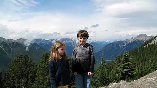 two little kids standing with the mountain and green trees background