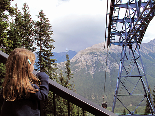 little girl on holding the rails looking at the mountain view and cable cars