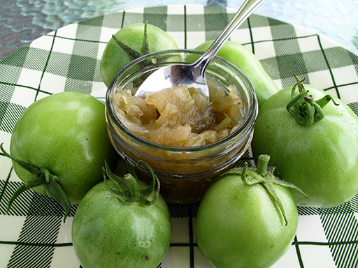 a cup of Green Tomato Relish around 6 pieces of fresh green tomatoes on a checkered green plate