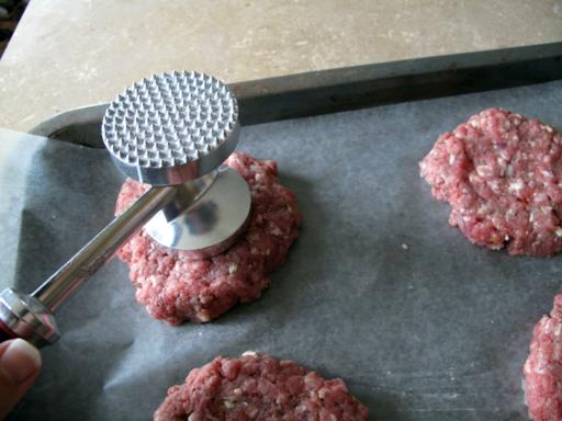 Pressing the center of the burgers down so they don't get that humpy