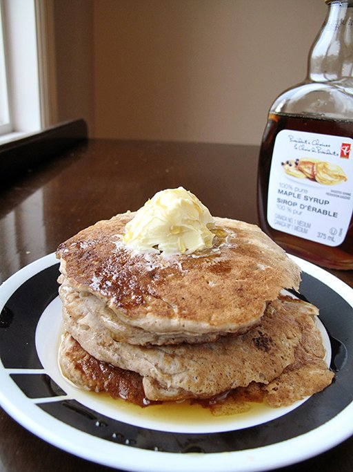 stack of Apple Pie Pancakes in a plate, topped with butter and maple syrup
