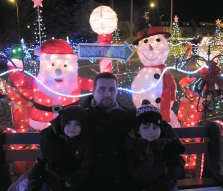 Dad with the kids sitting in the bench with lighted Santa and snowman