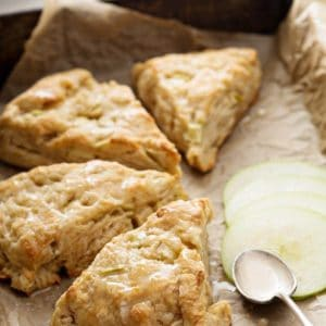 close up glazed pie shape Apple Scones with slices of tart apples on side