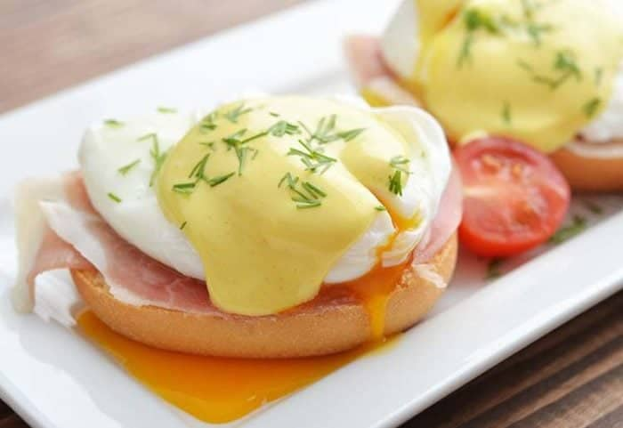 Eggs Benedict in white rectangular plate - poached egg over buttered muffin with a slice of bacon