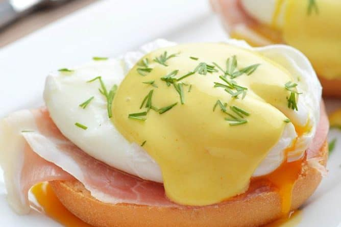 poached egg over buttered muffin with a slice of bacon topped with Hollandaise sauce