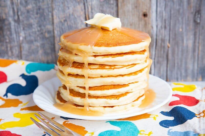 A stack of pancakes on a white plate with butter and syrup on top