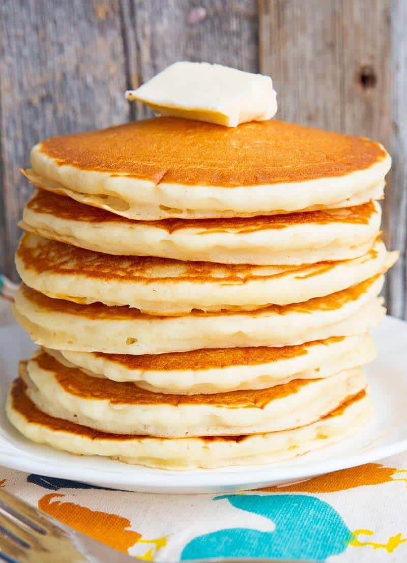 Close up of a stack of pancakes with butter on top