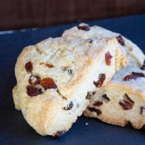 close up of scones with raisins on blue background