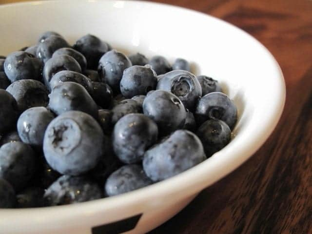 close up of blueberries for scones in a white bowl