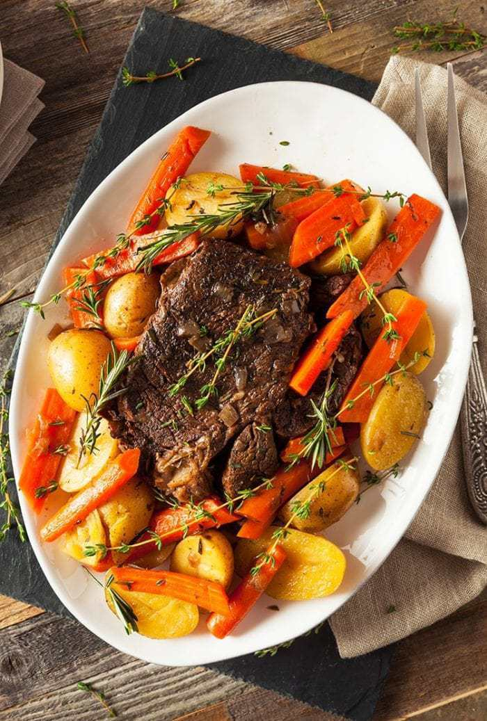 large white oval plate with Pot Roast in the center surrounded by different vegetables