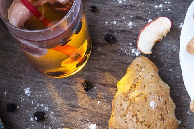 top down shot of ginger tea and scones in cute little tree shape on wood background