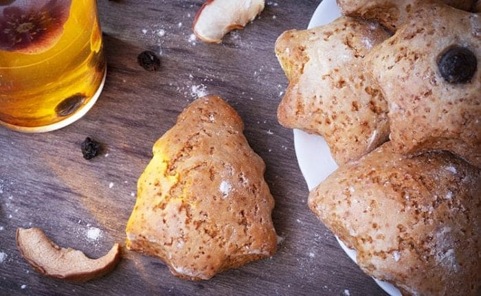 a plate of Ginger scones cut into adorable Christmas shapes! A glass of ginger tea on the side