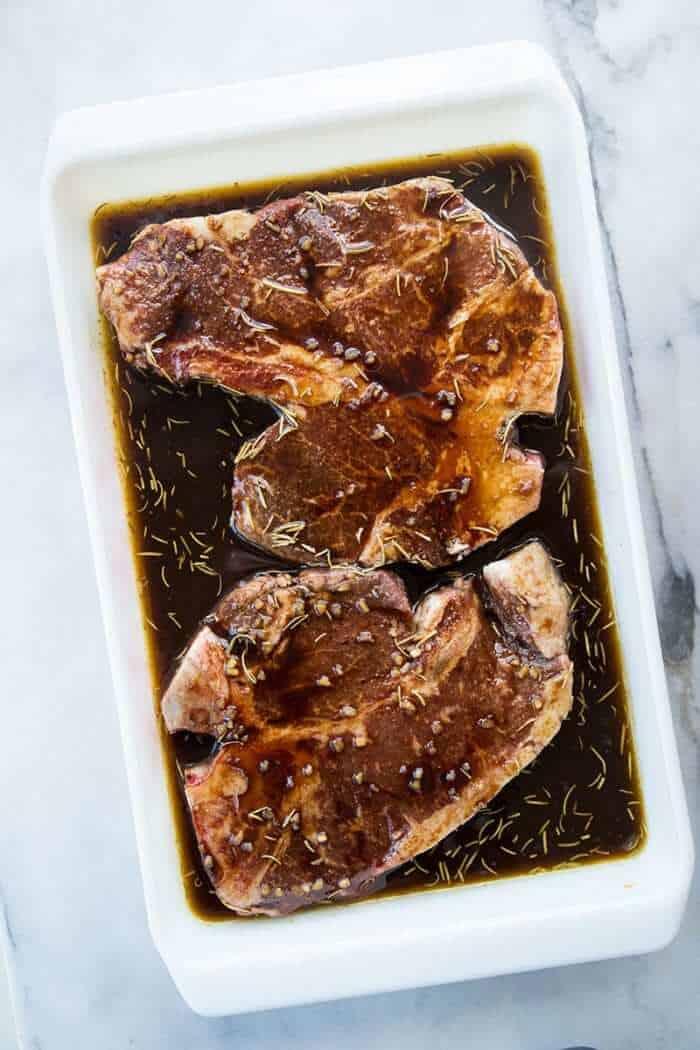 T-Bone steaks in the steak marinade in white pan