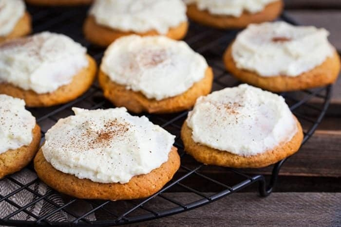 Frosted Pumpkin Drop Cakes! These cakey cookies are frosted with the BEST buttercream icing ever! Recipe from @kitchenmagpie #cookies #pumpkin #recipe #frosting #icing