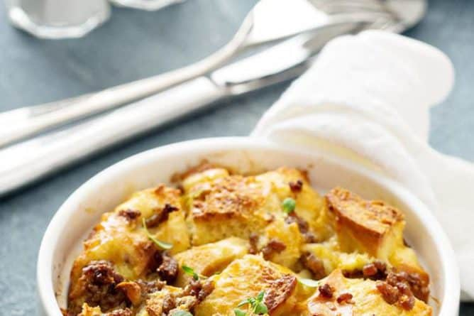 Sausage Breakfast Bake Casserole in a small white round baking dish. Fork, bread knife, salt and pepper shakers on background