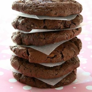 stack of White Chocolate Cocoa Cookies with parchment paper in between each piece