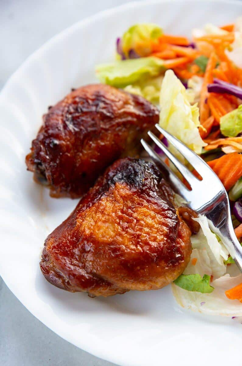 close up baked Teriyaki Chicken on a white plate with a fork and some vegetables