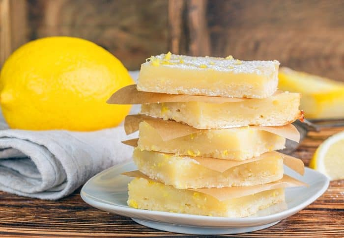 a stack of Creamy Lemon Bar slices in a white dessert plate, fresh lemon over white kitchen cloth on background