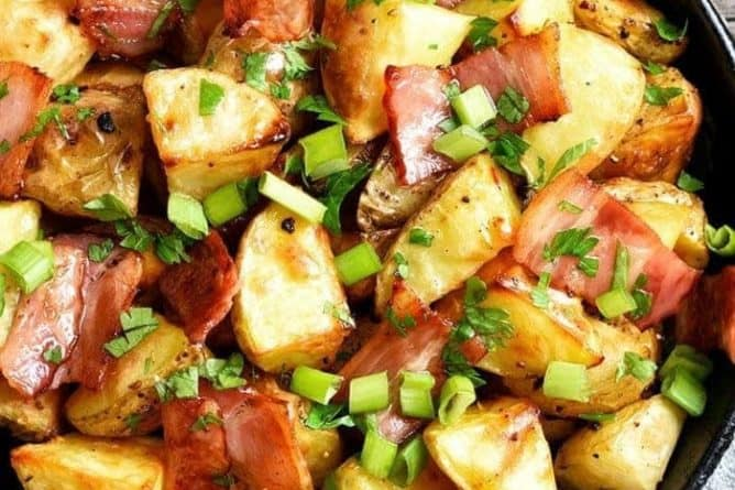 easy delicious skillet fried potatoes with bacon and green onions garnished with parsley placed on a light blue cloth on top of the table