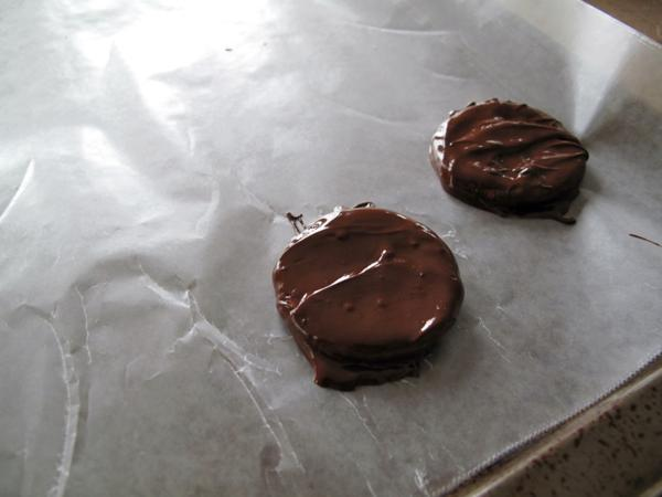 chocolate coated Ritz crackers place on the parchment paper