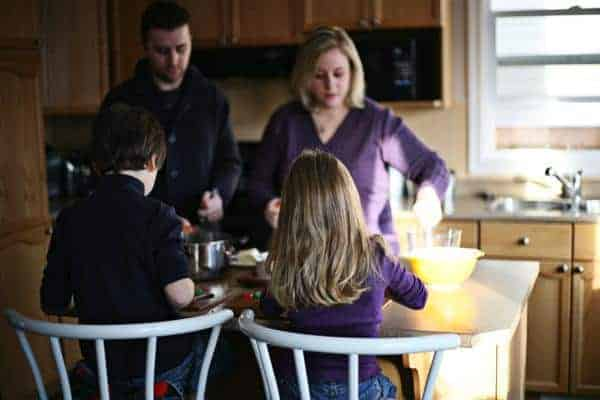 family picture in the kitchen preparing the Christmas Pudding