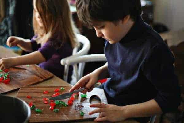 adorable children are chopping the candied cherries and pineapple rounds
