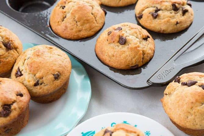 Banana muffins in a dark muffin tin and on a blue ruffled plate