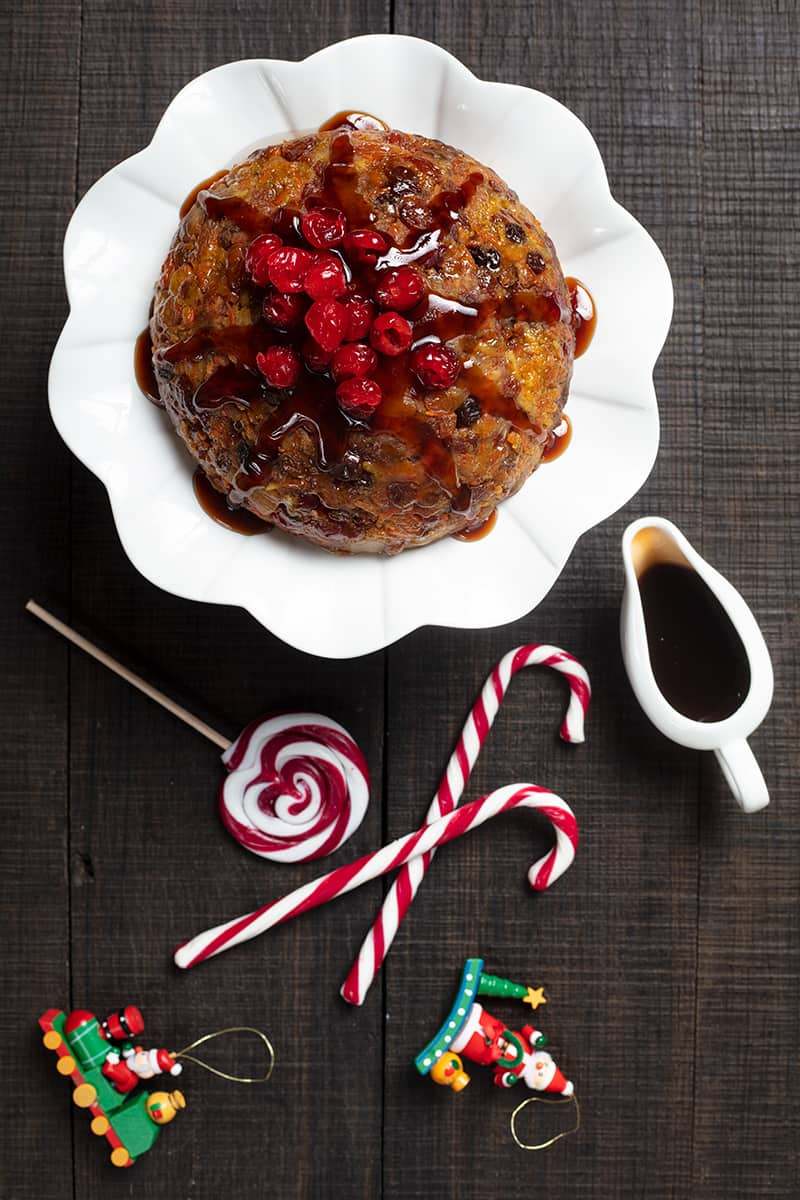 high angle shot of carrot Christmas Pudding on a white ceramic cake holder, brown sugar sauce on white mini pitcher and Christmas candy bars on sides