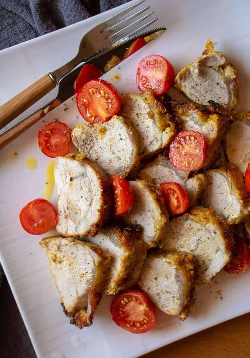 sliced Dijon Crusted Pork Tenderloin with some fresh tomatoes