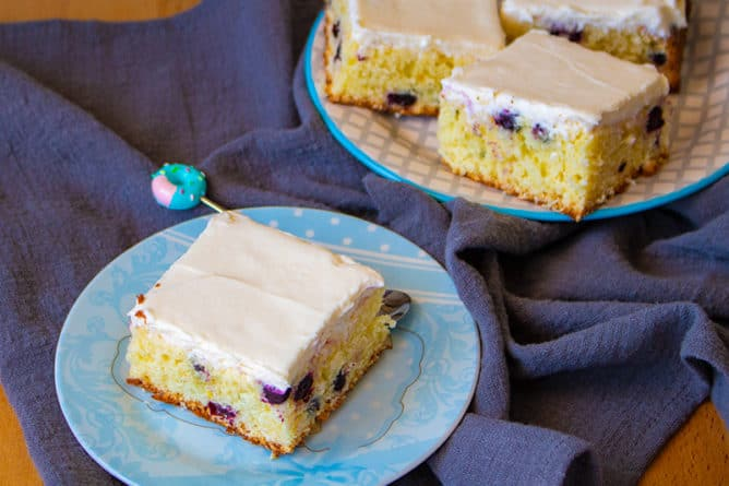 close up blue tablecloth underneath the plates of Lemon Blueberry Coffee Cake top with lemon butter cream icing
