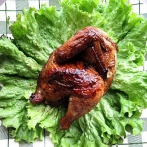 close up Honeyed Cornish Game Hens in a green checkered plate garnish with some lettuce leaves