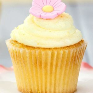Lemon Buttercream Frosting and pink icing flower on top of lemon cupcake