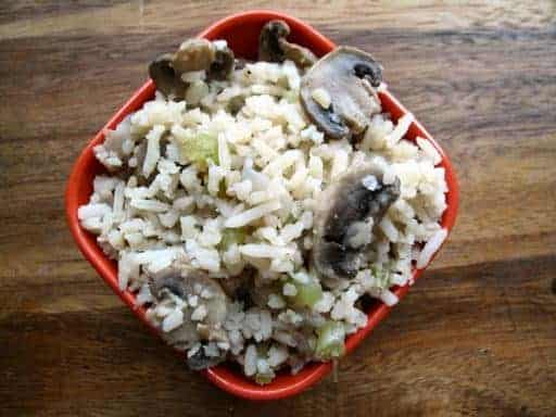 non-creamy version of Rice & Mushroom Casserole in a red bowl on wood background