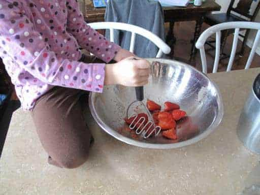 crushing the strawberries in a large bowl