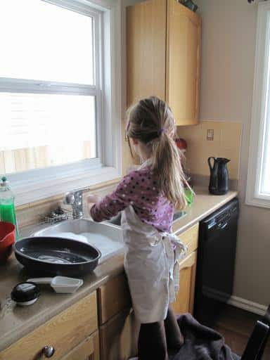 a little girl with apron in the kitchen washing her hands