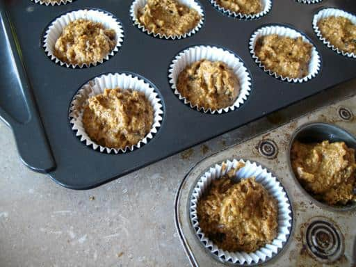 muffin tins with paper liners filled with Pumpkin Bran Muffin dough
