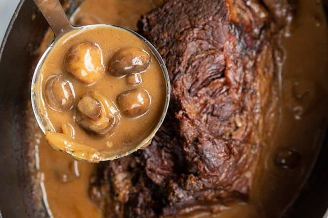 Creamy Mushrooms and Gravy in a Ladle from a slow cooker with Cooked Chuck Roast