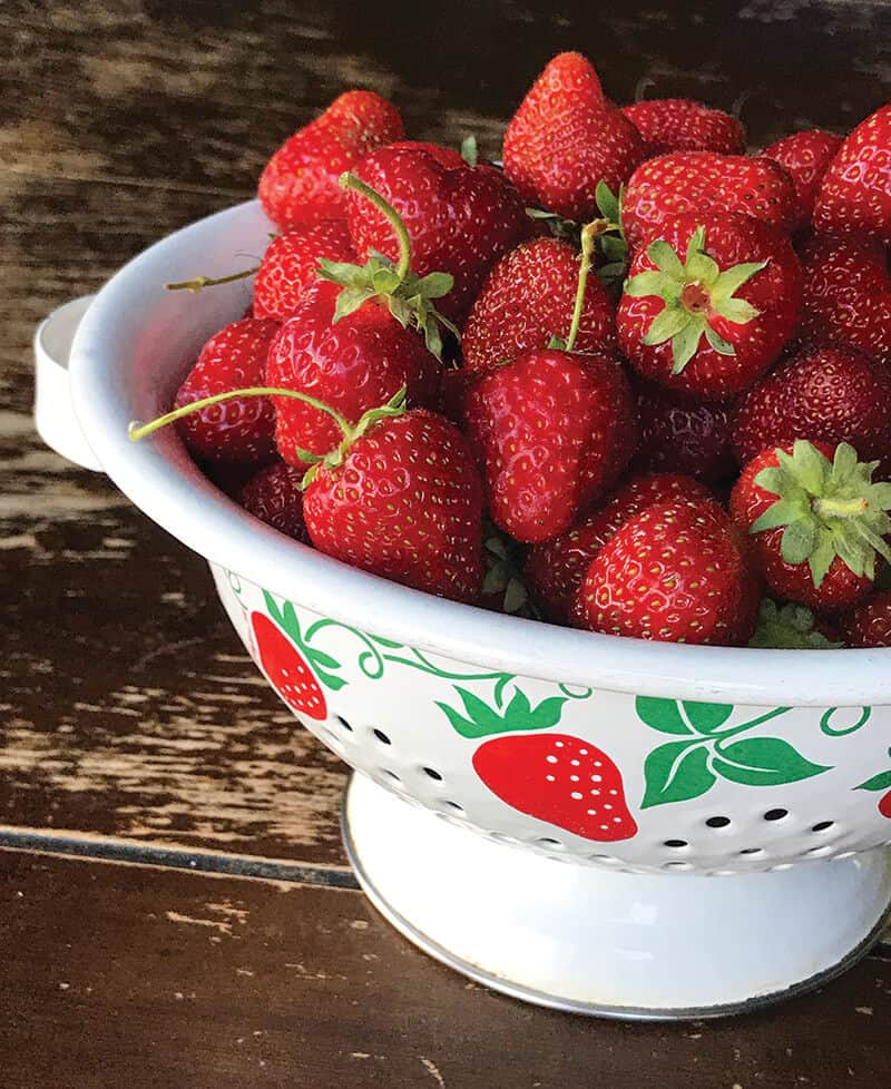 fresh strawberries in strainer bowls