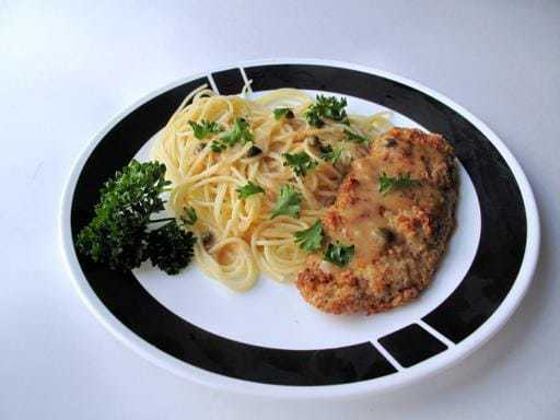 Chicken Picatta served over warm angel hair pasta and topped with fresh parsley