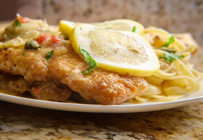 Chicken Francaise over pasta topped with slices of lemon and fresh parsley