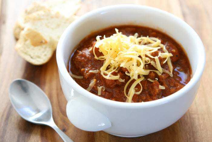 Kitchen Sink Crockpot Chili in a white bowl with grated cheese on top