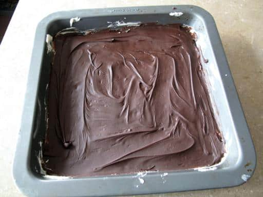 chocolate spread all over the crumbs in a baking pan