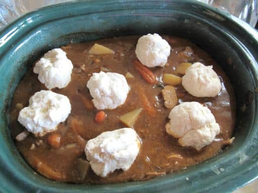 Dumpling batters on the top of stew/soup concoction in the crockpot