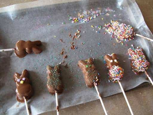 Chocolate coated bunny peeps with colorful sprinkles in a baking sheet with parchment paper
