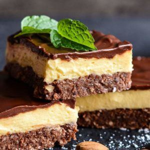 close up 3 pieces nanaimo bars, mint leaves and walnuts
