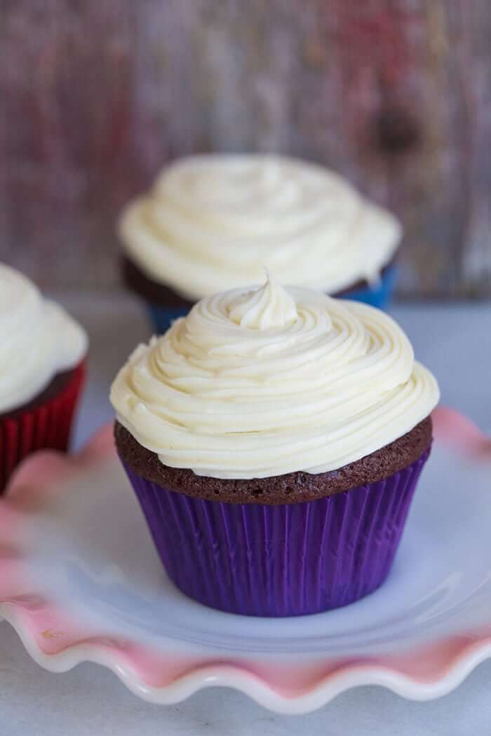 cupcake in a white plate with cupcake liner and Cream Cheese Icing swirled on top, more cupcakes with cream cheese icing on the background