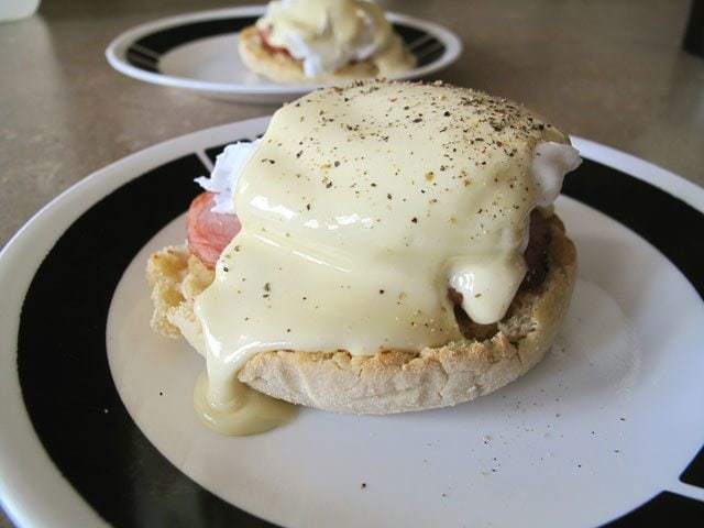 Plate with Eggs Benedict topped with Hollandaise Sauce